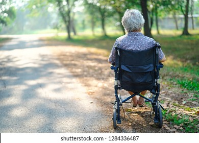 Asian senior or elderly old lady woman patient on wheelchair in park : healthy strong medical concept
