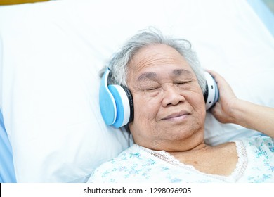 Asian senior or elderly old lady woman patient  listen to music while lie down on bed in nursing hospital ward : healthy strong medical concept