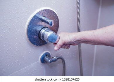 Asian senior or elderly old lady woman patient use toilet bathroom to open shower in nursing hospital ward : healthy strong medical concept.