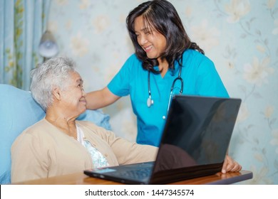 Asian senior or elderly old lady woman patient using notebook computer and smile with doctor while sitting on bed in nursing hospital ward : healthy strong medical concept