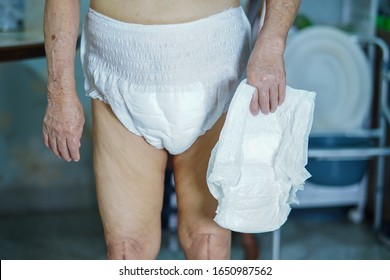 Asian senior or elderly old lady woman patient wearing incontinence diaper in nursing hospital ward : healthy strong medical concept.