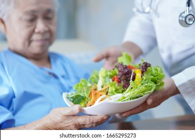 Asian senior or elderly old lady woman patient eating breakfast vegetable healthy food with hope and happy while sitting and hungry on bed in hospital.