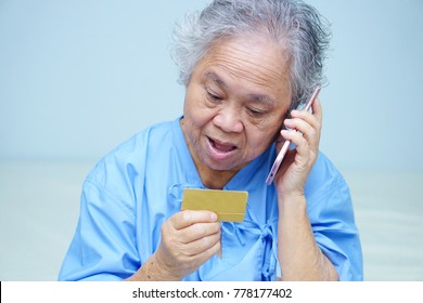 Asian senior or elderly old lady woman patient with credit card talking on the mobile phone while sitting and happy on bed in nursing hospital.