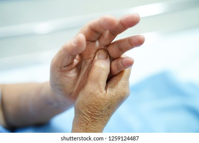 Asian senior or elderly old woman patient pain finger and hand while sitting on bed in nursing hospital ward : healthy strong medical concept.