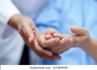 Asian senior or elderly old woman patient pain trigger finger lock her hand while sitting on bed in nursing hospital ward : healthy strong medical concept.