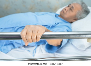Asian senior or elderly old woman patient lie down handle the rail bed with hope on a bed in the hospital.