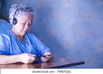 Asian senior or elderly old woman patient holding tablet in her hands to Listen and read news and music with headphones while sitting on bed in hospital.