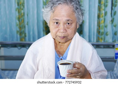 Asian senior or elderly old woman patient holding a cup of coffee in her hands on breakfast while sitting on bed in hospital.