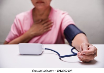 Asian Senior Female checking her pulse and measuring blood pressure with herself. Health care. Stressed. Worried.