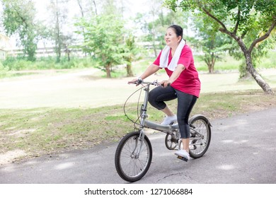asian senior female cycling in public park, she feeling happy and healthy, retirement health promotion