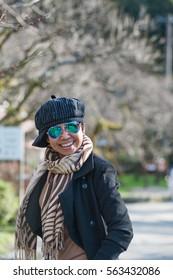 Asian senior female tourist in winter costume traveling in Dazaifu temple, Japan