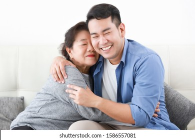 Asian senior grand mother with son happy and smile on the sofa in living room love family concept