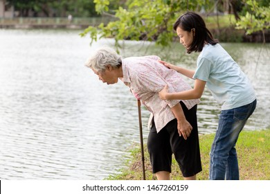 Asian senior grandmother about to throw up,vomit,puke retch barf,feeling sick from indigestion or food poisoning,elderly woman with child girl or granddaughter helping,care her in outdoor,health care