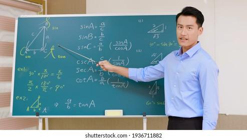 asian senior high school male teacher teach math online through webcam in classroom
