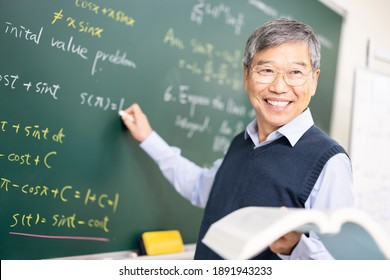 asian senior male calculus professor is writing on blackboard in the classroom at college