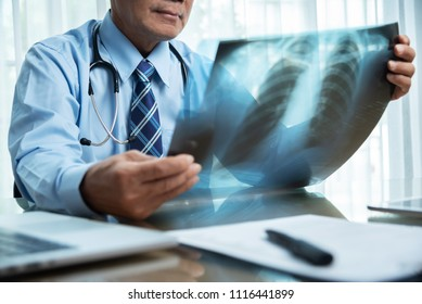 Asian Senior Male doctor in blue shirt looking to x-ray film at a medical room.