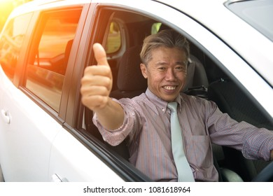 asian senior male driving with thumbs up