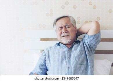 Asian Senior male suffering from bad pain in his have a Neck pain at home - senior healthcare concept