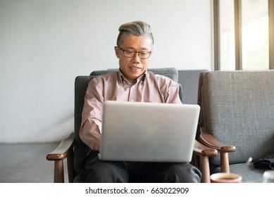 asian senior male using laptop on cafe