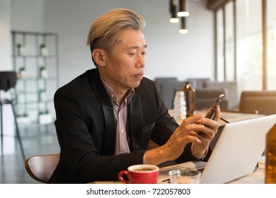 asian senior male using laptop and phone in cafe