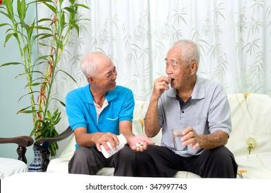 Asian senior man having medicine at home. Adult son caring for a senior man.