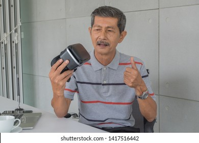 Asian senior man, Holding VR glasses with Feeling happy for modern technology. front on the desk. there are white coffee mug and laptop computer, pen in the office room.