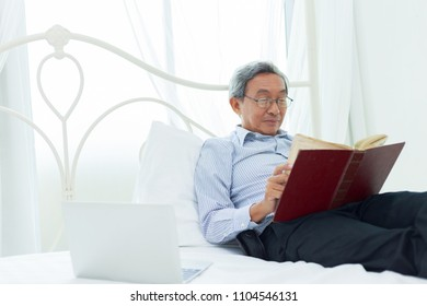 Asian senior man lying and reading book on bed in bedroom. Ederly people relaxed lifestyle after retried working.