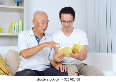 asian senior man reading a book with his son at home