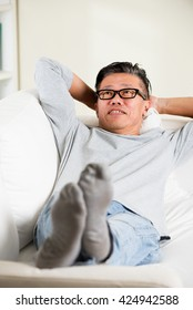 asian senior man relaxing on sofa at home