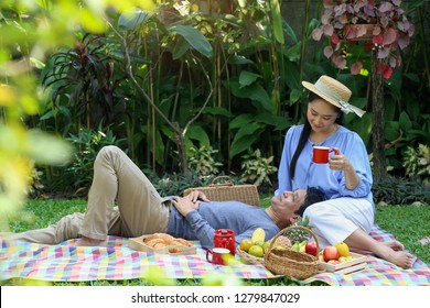 Asian senior man rest on lap of his wife among the green garden in the picnic weekend, valentine's day, retirement activity, family time, relaxation and couple lifestyle.