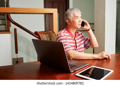 Asian senior man talking on mobile phone while working with laptop computer and tablet pc at the table at home