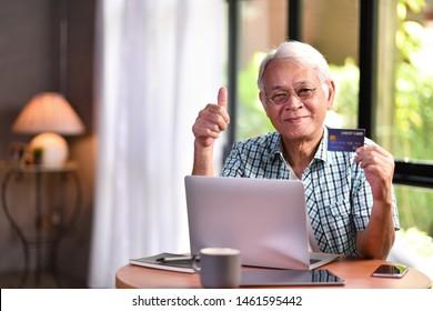 Asian senior man using credit card for online shopping