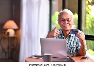 Asian senior man using credit card for online shopping