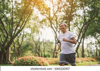 Asian senior mature man running Jogging In Park