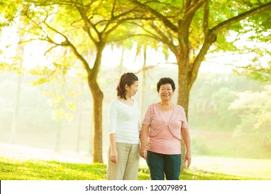 Asian senior mother and adult daughter walking at outdoor green park