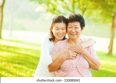 Asian senior mother and adult daughter at outdoor park