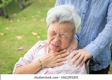 Asian senior mother have nerve pain,shoulder and neck pains,female caregiver or daughter massaging her shoulders elderly woman,feeling painful,muscle soreness,inflammation,shoulder ache in wheelchair