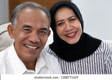 asian senior muslim couple sitting on the sofa and smiling to the camera