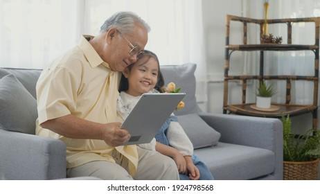 Asiatischer Senior, der nach Tablet Computer sucht, und Enkelin kommen zu Hause, Großvater liest Nachrichten über digitale Tablette mit seinem Kind auf Sofa im Wohnzimmer