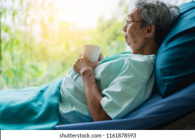asian senior patient man take a rest with hot tea on hospital bed health ideas concept