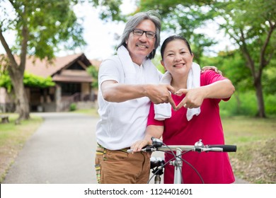 Asian senior people exercise in public park, they show heart sign with hand, they feeling happy and smiling, healthy activity, retirement happiness
