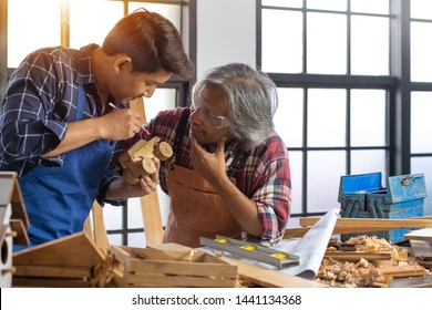 Asian senior professional carpenter and young carpenter with finished making car wood toy in hand, checking the ready good, Concept of woodworking