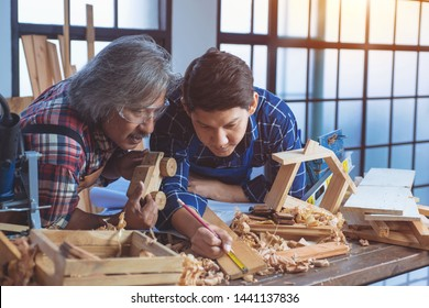 Asian senior professional carpenter and young carpenter with finished making car wood toy in hand, young carpenter measuring wooden plank with measuring tape, Concept of woodworking