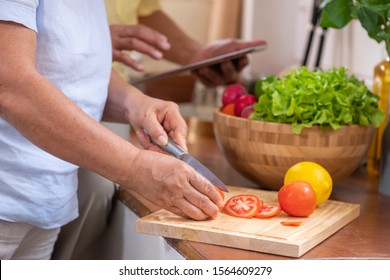 Asian senior wife slicing tomatoes on wooden cutting  board and using tablet computer to searching menu recipe.senior with technology lfiestyle.aging at home