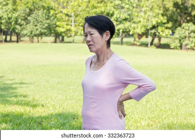 Asian senior woman back pain in the park