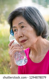 Asian senior woman with a bottle of drinking water.
