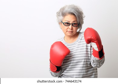 The Asian senior woman with boxing gloves on the white background.