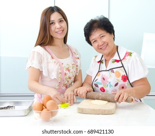 Asian senior woman and daughter prepare for baking in the kitchen