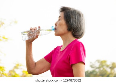 Asian senior woman drinking water from the bottle.