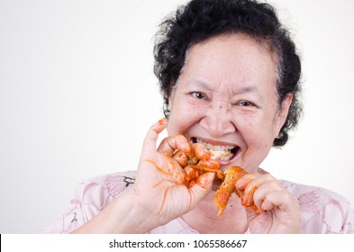 Asian Senior woman eat fried chicken over white background